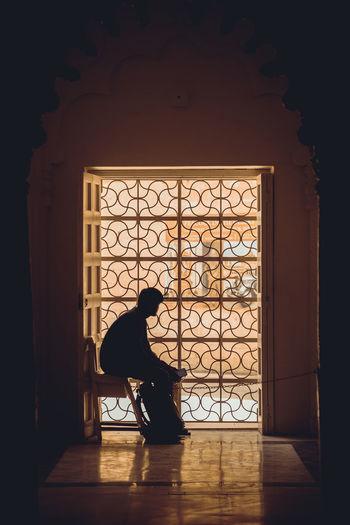 Side view of silhouette man sitting inside a caged door