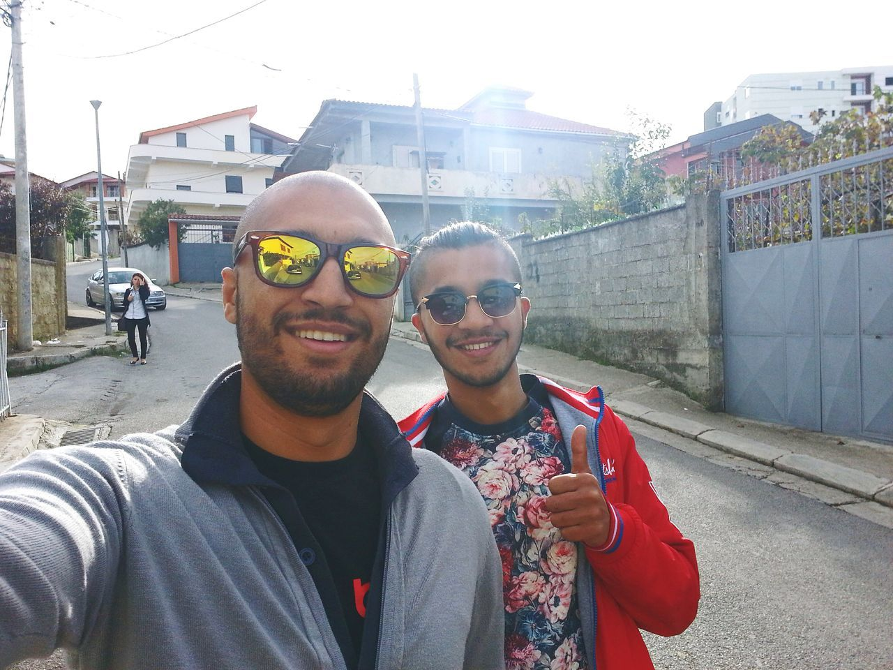 looking at camera, smiling, portrait, happiness, real people, two people, built structure, young adult, architecture, lifestyles, young men, day, leisure activity, mid adult men, togetherness, building exterior, front view, outdoors, casual clothing, selfie, bonding, standing, cheerful, technology, men, young women, city, people