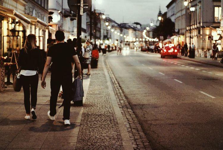 Rear view of people walking on sidewalk by street amidst buildings in city