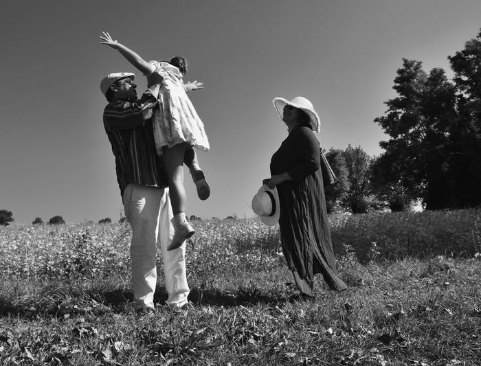 Father Lifting Her Daughter While Standing On Field Against Sky