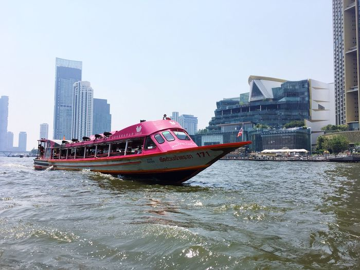 Boat in river by buildings against clear sky