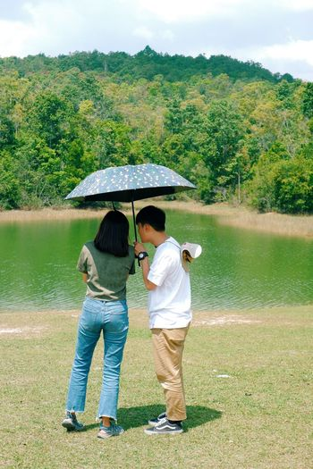 Rear view of couple standing by lake against trees