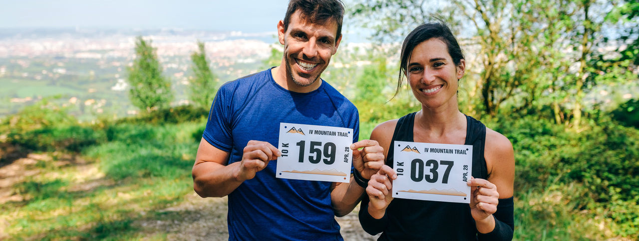 Portrait of happy couple holding marathon bibs while standing on field