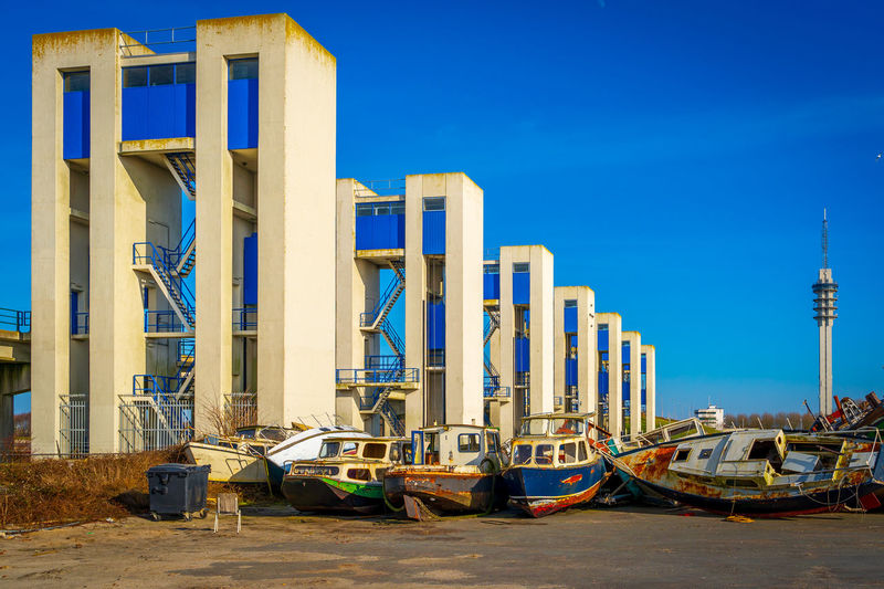 Boats moored at pier against blue sky
