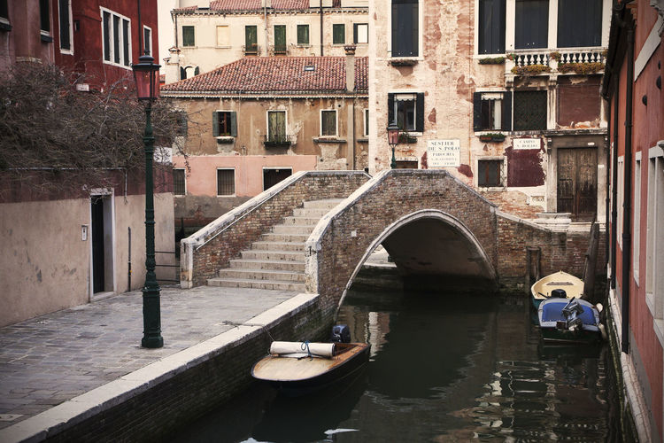 Old bridge in Venice crossing a traditional canal Venice Venice, Italy Venezia Italy City Cityscape Landmark Famous Place Travel Destinations Canal Canal In Venice Venetian Canal Boats Houses Building Bridge Bridge - Man Made Structure Water Lagoon Arch Bridge Day Architecture