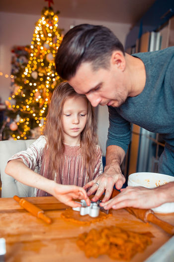 Father assisting daughter in making christmas cookies on table at home