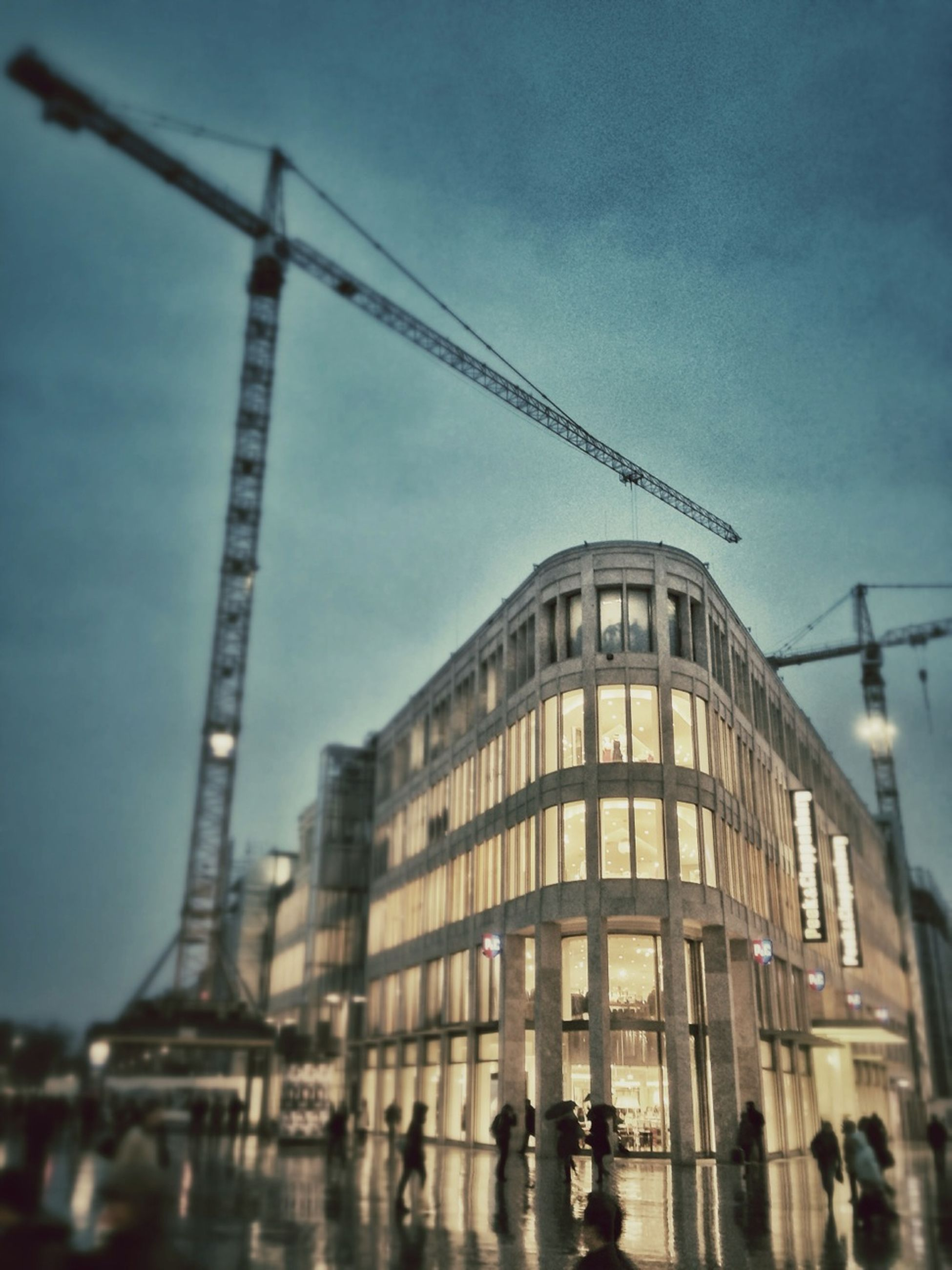 architecture, building exterior, built structure, city, sky, low angle view, building, city life, outdoors, transportation, crane - construction machinery, street, day, men, office building, dusk, street light, incidental people, residential building