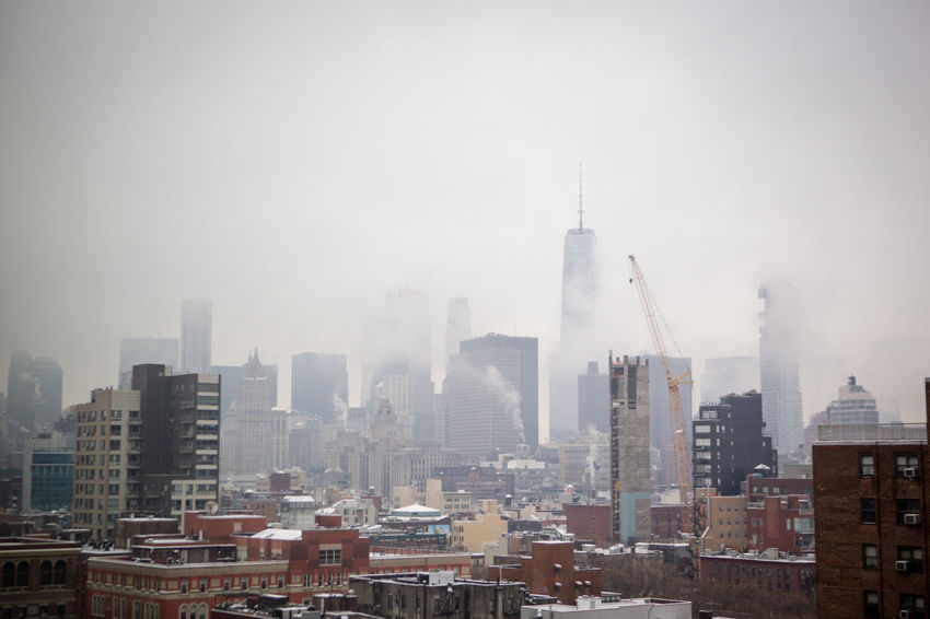 New York City skyline on a snowy day, from the Lower East Side Architecture Building Exterior City Cityscape Day Downtown District Fog January Mist Misty No People Outdoors Sky Skyscraper Snow Travel Destinations Urban Skyline Winter
