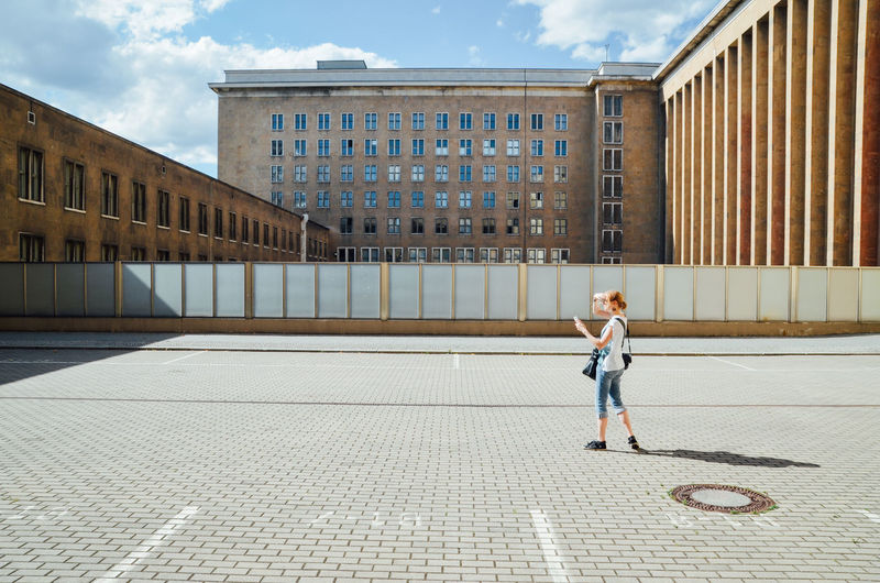 Full Length Side View Of Woman Photographing On Street Against Buildings