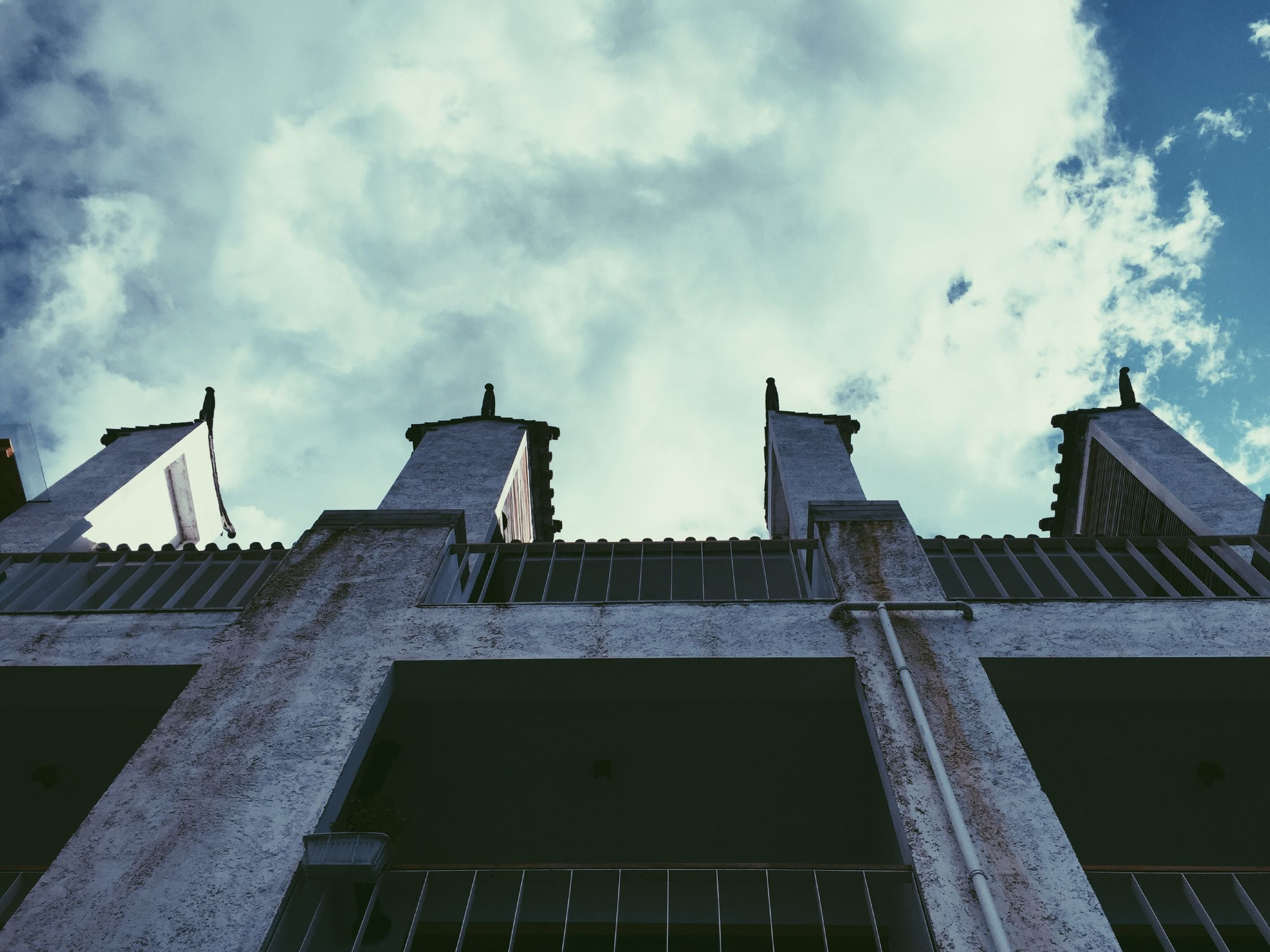 architecture, low angle view, built structure, building exterior, sky, cloud - sky, cloud, city, building, outdoors, day, no people, high section, cloudy, window, history, tower, sunlight, architectural feature, residential building
