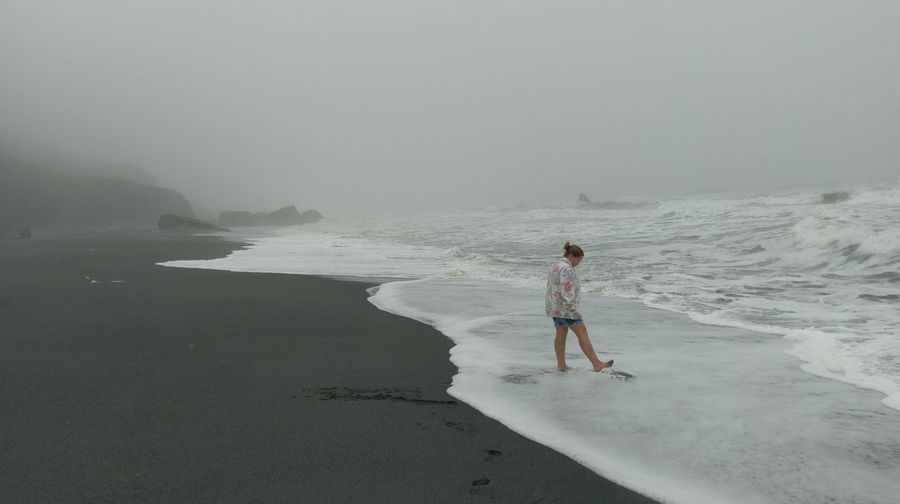 Woman standing at beach against foggy sky during stormy weather