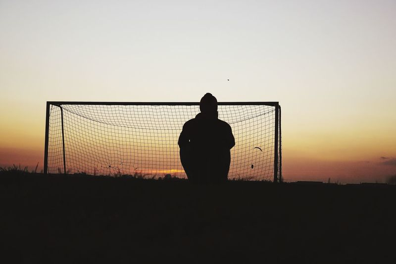Silhouette man sitting by net at soccer field against sky during sunset