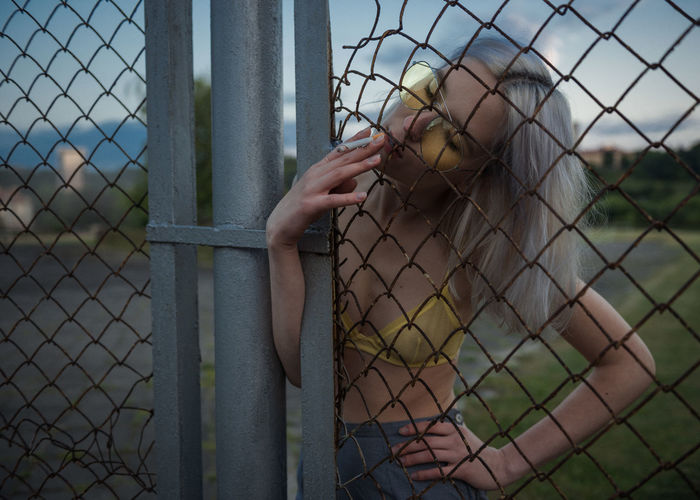 Woman smoking cigarette at chainlink fence