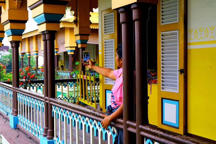 Istana maimun One Person Architecture Lifestyles Built Structure Building Exterior Leisure Activity Day Building Yellow Communication Standing Casual Clothing Railing Women Holding Adult Outdoors Men Architectural Column Istana Maimun EyeEmNewHere
