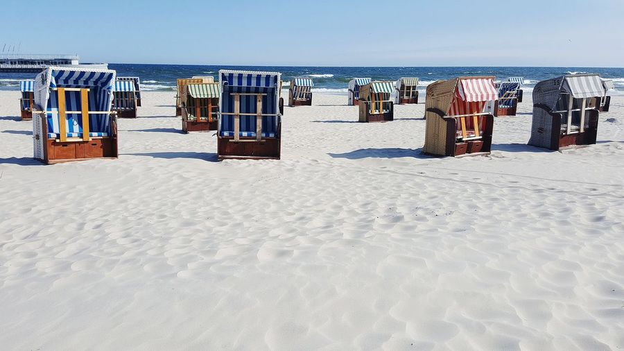 Hooded Chairs On Beach Against Sky
