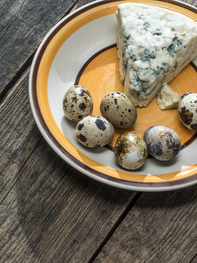 Quail eggs and roquefort cheese on a plate on an old wooden weathered table Wooden Quail Eggs Weathered Blue Bowl Cheese Close-up Day Directly Above Food Food And Drink Freshness Healthy Eating High Angle View Indoors  No People Old Old Buildings Plate Ready-to-eat Roquefort Table Wood - Material