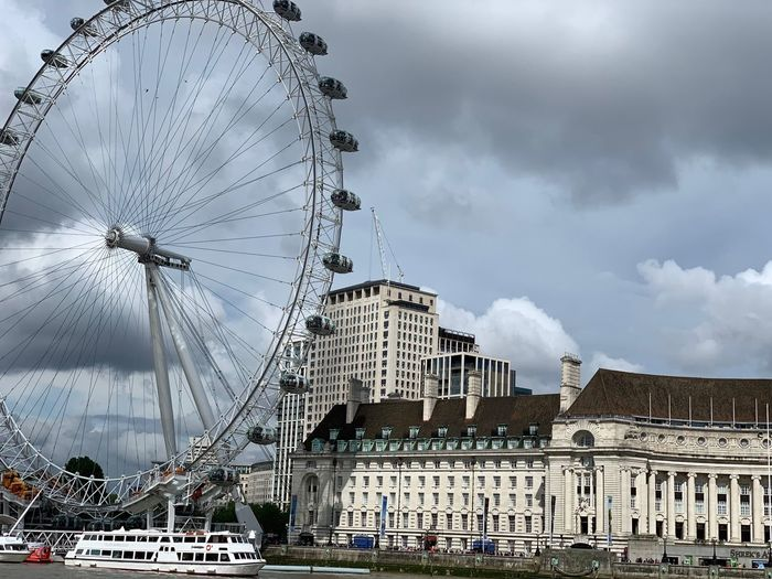 Low angle view of ferris wheel in city against cloudy sky