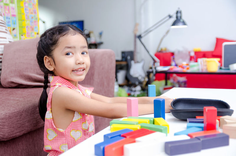 Happy Asian little girl playing wooden brick Childhood Cute Day Focus On Foreground Girls Happiness Home Interior Indoors  Leisure Activity Lifestyles Looking At Camera Multi Colored One Person Playing Portrait Real People Smiling Toy Block