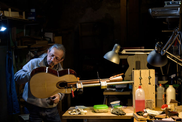 The Luthier of Siena -- In a small village near the city of Siena, Tuscany, Italy, a luthier puts the finishing touches on a guitar he created in his dimly lit workshop. Artisan Italia Luthier Tuscany Expertise Guitar Indoors  Instrument Maker Italian Italian Lifestyle Italy Music Musical Instrument One Person Real People Siena Skill  String Instrument Village Workshop