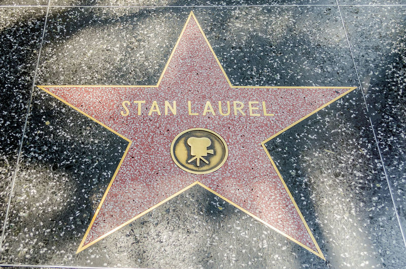 HOLLYWOOD - AUGUST 26, 2012: Stan Laurel's star on Hollywood Walk of Fame, as seen on August 26, 2012 in Hollywood in California. This star is located on Hollywood Blvd. and is one of 2400 celebrity stars. Arrow Symbol City Close-up Communication Day Direction Directional Sign Guidance Information Information Sign No People Outdoors Road Road Sign Shape Sign Star Shape Symbol Text Transportation Warning Symbol