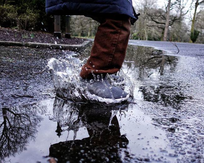 Low section of man splashing water in puddle