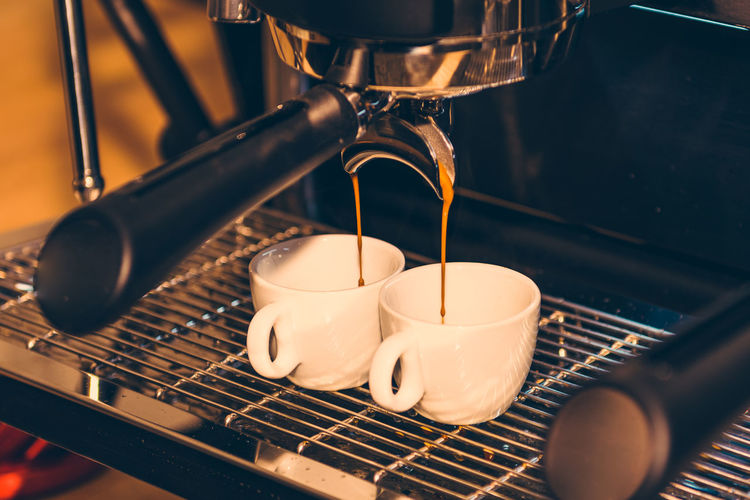 Close-Up Of Drink Pouring In Cups On Espresso Maker
