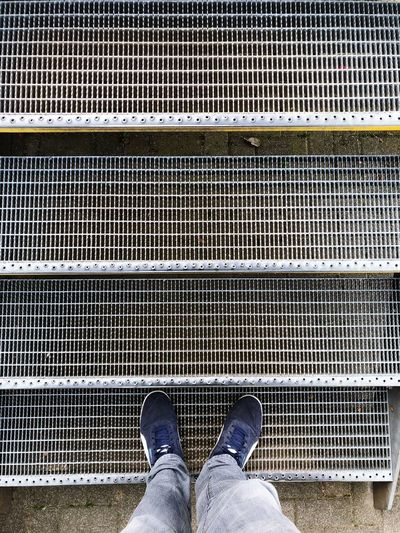 Low Section Of Man Standing On Metal Steps