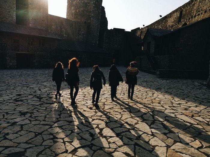 Women walking on street by historical building
