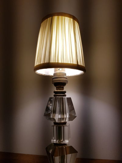 Close-up of illuminated electric lamp on table at home