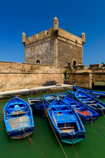 Blue boats moored in canal by castle against clear blue sky during sunny day