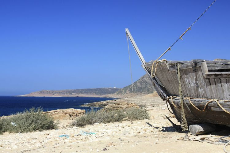 Cropped boat moored at beach against clear blue sky