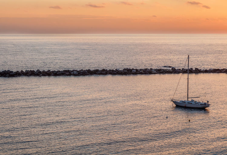 Sailboat on sea against sky during sunset