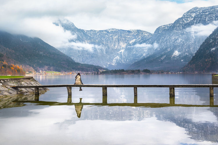 Rear view of woman sitting on bridge over hallstatter see against mountains in hallstatt