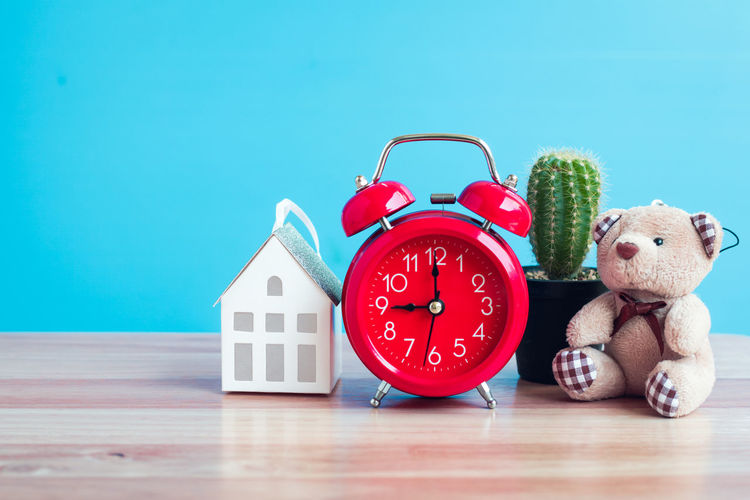 Close-Up Of Clock And Model House With Teddy Bear On Table Against Wall