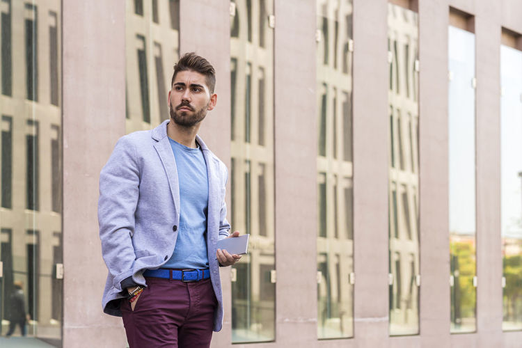 Portrait of young man standing against building in city
