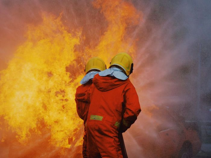 Clothing Smoke - Physical Structure One Person Burning Fire Rear View Fire - Natural Phenomenon Firefighter Men Occupation Nature Standing Accidents And Disasters Real People Flame Day Protection Heat - Temperature Headwear Outdoors Uniform Rescue Worker Hood - Clothing