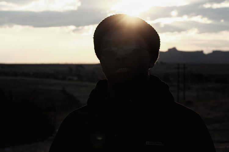 Close-up portrait of silhouette man against sky during sunset