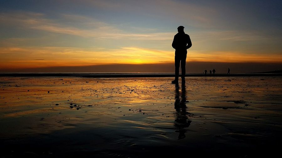 Silhouette of man standing on beach looking into sunset