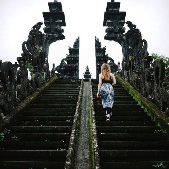 exploring Pura Besakih, the holiest and largest Hindu temple in Bali Girl Exploring Temple Sarong Temples Hindu Bali Ancient Architecture Religious Architecture Architecture Stairs Vanishing Point Climbing