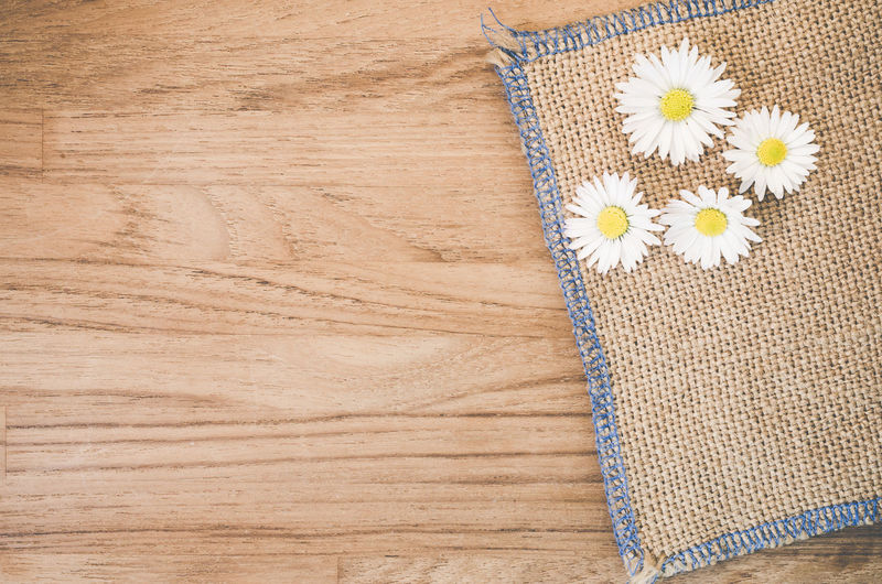 Directly above shot of daisy flowers with jute on hardwood floor