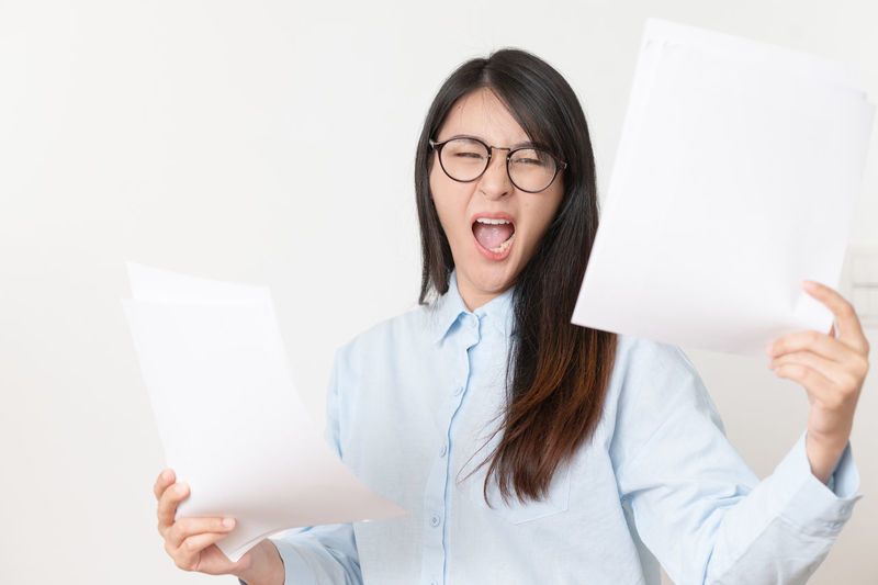 Midsection of woman holding paper against white wall