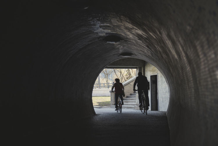 silhouette of two cycling people going out of a tunnel of an old city Adult Arch Architecture Built Structure Ceiling Day Direction Full Length Group Of People Indoors  Lifestyles Light At The End Of The Tunnel Men People Real People Rear View Silhouette The Way Forward Transportation Tunnel Walking Women