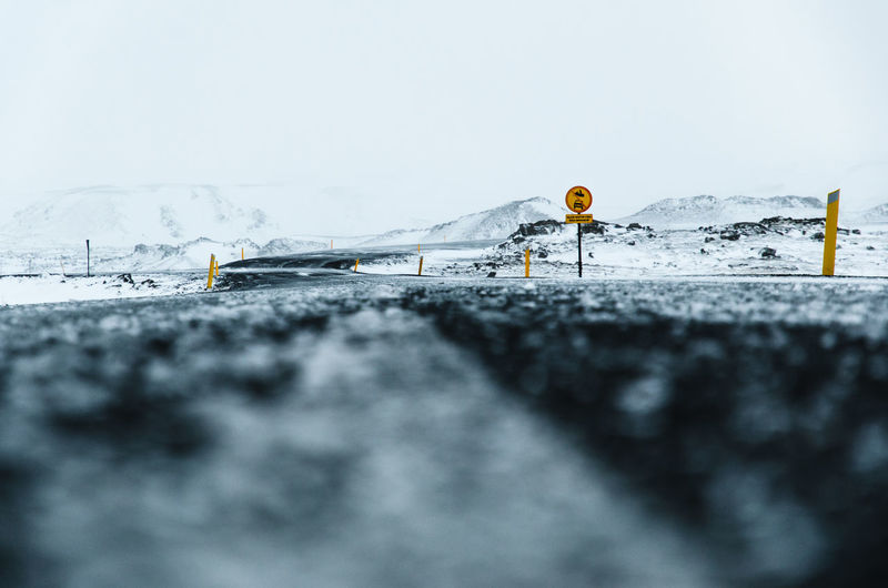 Close-up of snow on road against sky