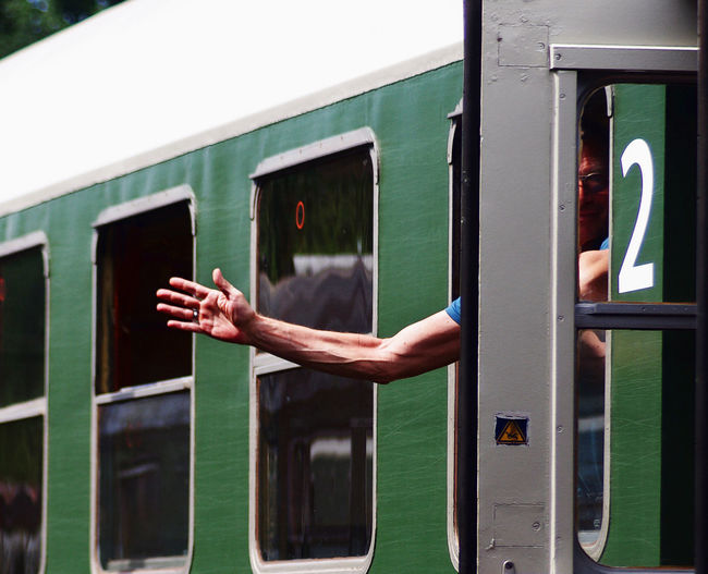 Cropped Hand Of Man Gesturing From Train Window
