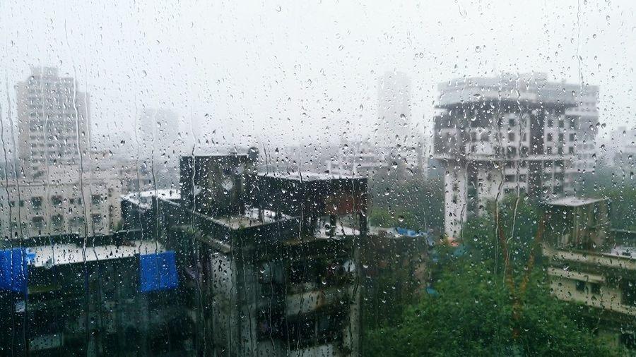 Buildings Seen Through Wet Window In Rainy Season