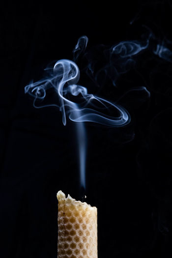Close-up of candle against black background