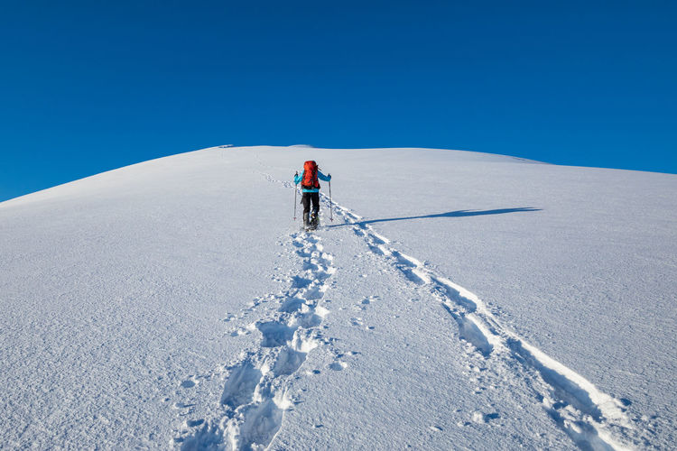 Rear view of person climbing on snowcapped mountain against clear sky