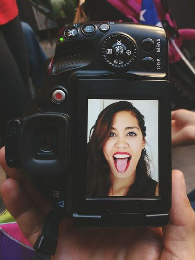 Cropped image of hand holding camera with woman sticking out tongue on screen