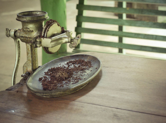 High angle view of cocoa grinder on wooden table
