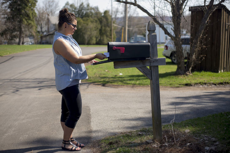 Side view of young woman standing by mailbox on street